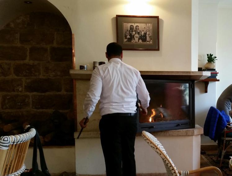 המלצר ממלא את האח בבולי עץ